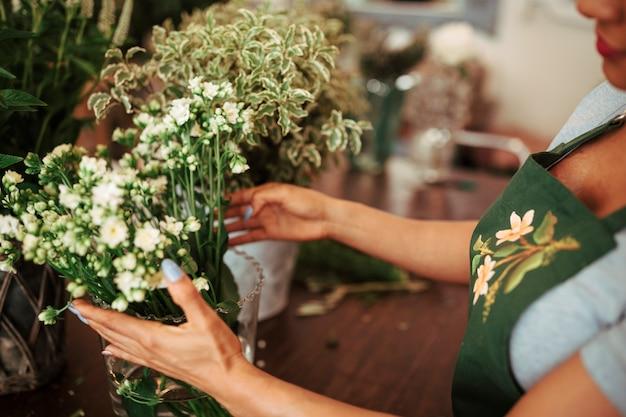 Vrouw die bos van bloemen in vaas schikken Gratis Foto