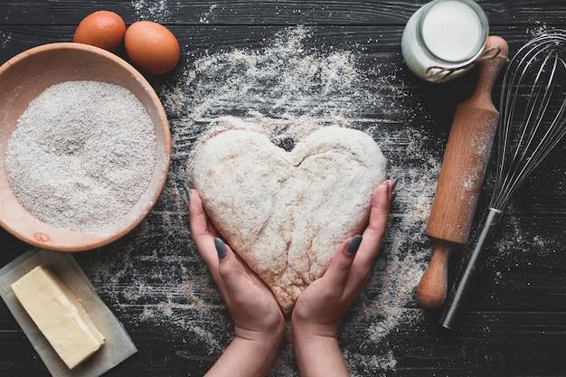 Vrouw die brood in hartvorm maakt Premium Foto