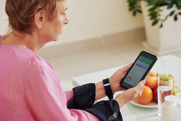 Vrouw die calorieteller controleert Premium Foto