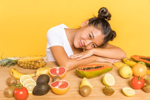 Vrouw die camera bekijkt die door vruchten wordt omringd Gratis Foto