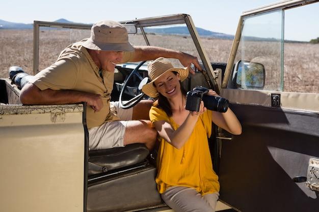 Vrouw die camera toont aan de mens in voertuig Gratis Foto