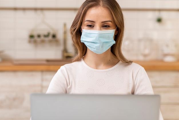 Vrouw die chirurgisch gezichtsmasker en laptop draagt Gratis Foto