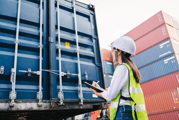 Vrouw die containerdoos voor logistisch controleert Premium Foto