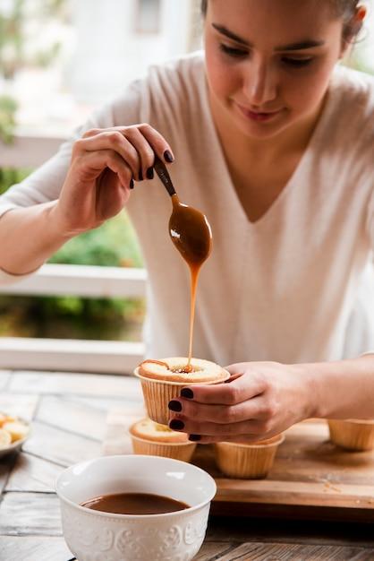 Vrouw die cupcake met lepel vult Gratis Foto