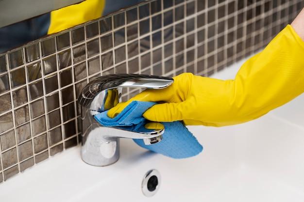 Vrouw die de badkamersgootsteen schoonmaakt Gratis Foto