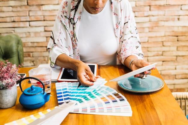 Vrouw die de ceramische plaat met kleurenmonster aanpassen op houten lijst Gratis Foto