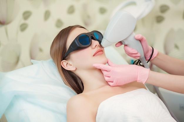 Vrouw die de gezichtslaser van de haarverwijdering heeft Premium Foto