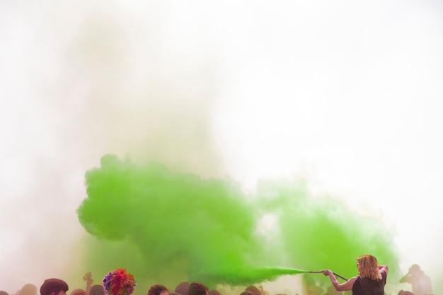 Vrouw die de groene holikleur met pijp over de menigte bespuiten Gratis Foto