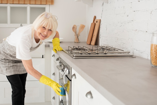 Vrouw die de keuken met handschoenen schoonmaakt Gratis Foto