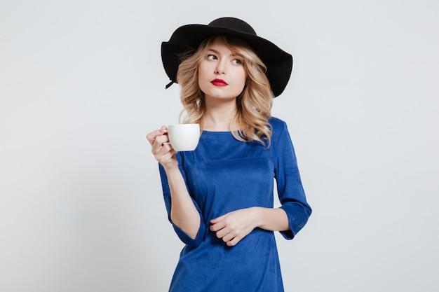 Vrouw die de kop van de hoedenholding van koffie draagt Gratis Foto