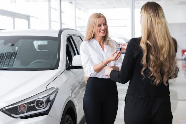 Vrouw die de sleutel van de nieuwe auto ontvangt Gratis Foto