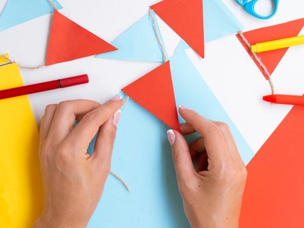 Vrouw die decoratie met rood en blauw document maakt Gratis Foto