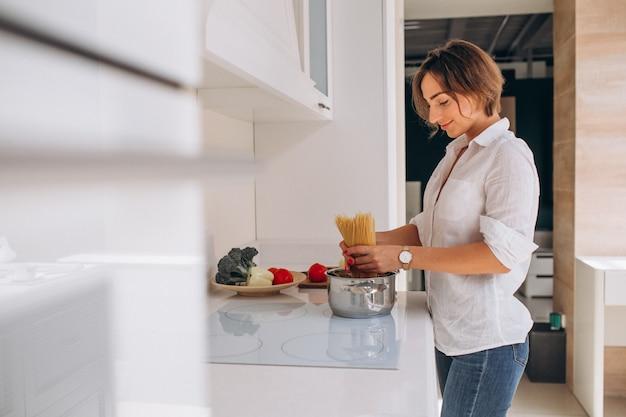 Vrouw die deegwaren voor diner maken bij de keuken Gratis Foto