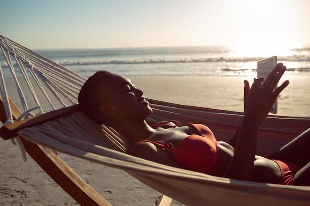 Vrouw die digitale tablet gebruiken terwijl het ontspannen in een hangmat op het strand Gratis Foto