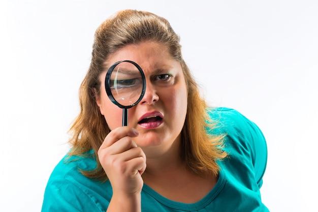 Vrouw die door vergrootglas of loupe kijkt Premium Foto