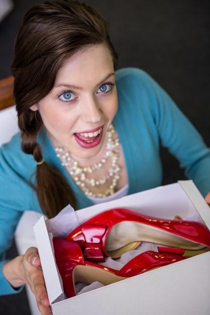 Vrouw die doos met rode schoenen toont Premium Foto