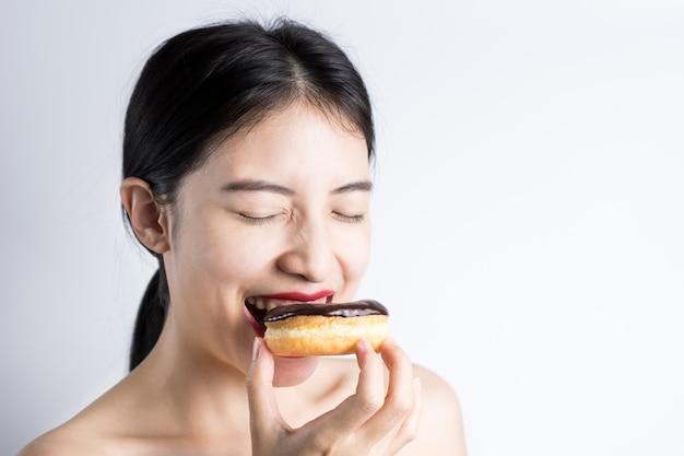 Vrouw die doughnut op witte achtergrond eet Premium Foto