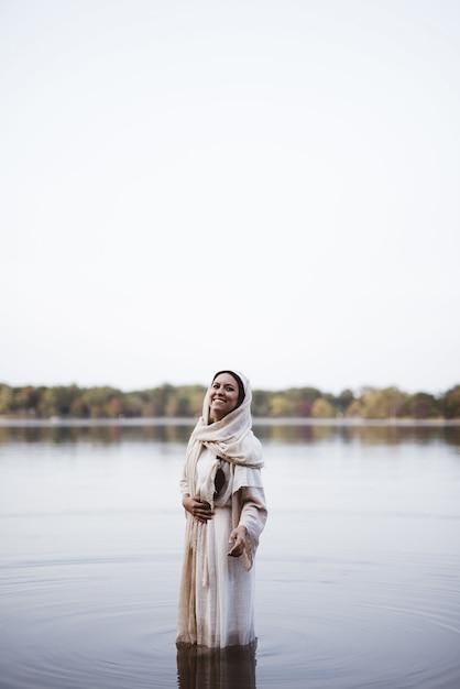 Vrouw die een bijbels gewaad draagt terwijl status in het water en het glimlachen Gratis Foto