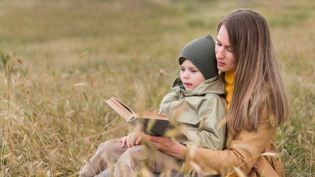 Vrouw die een boek buiten leest aan zijn zoon Gratis Foto