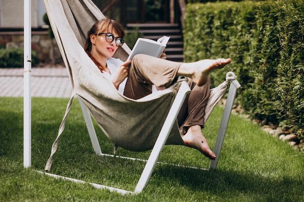 Vrouw die een boek in de tuin door het huis leest Gratis Foto