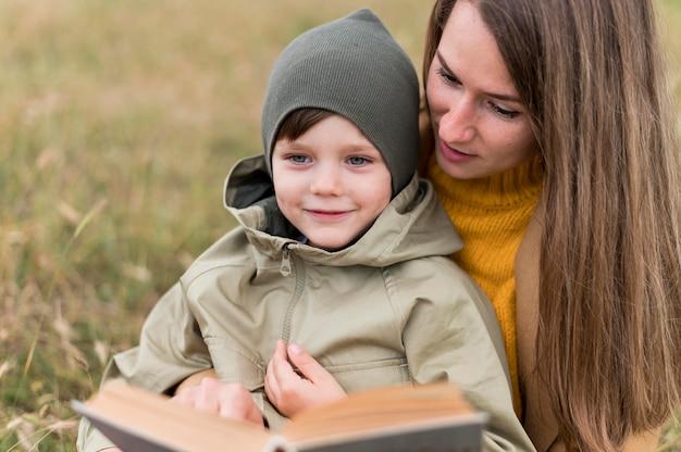 Vrouw die een boek leest aan zijn zoon Gratis Foto