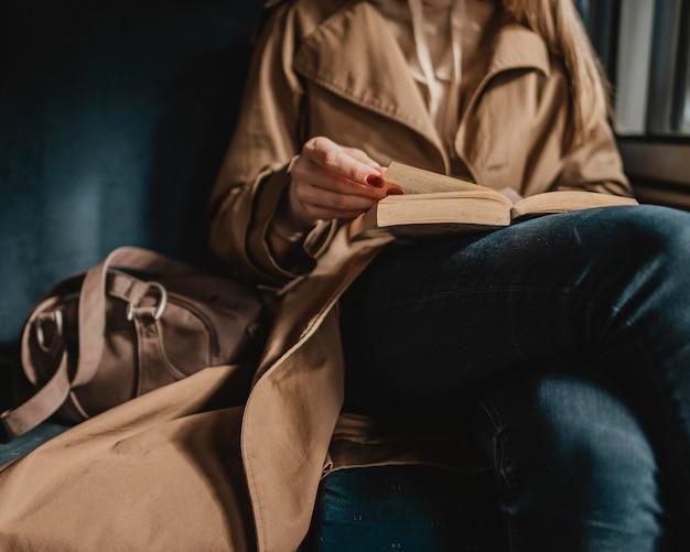 Vrouw die een boek leest in een trein Gratis Foto
