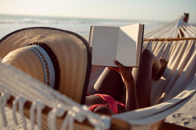 Vrouw die een boek leest terwijl het ontspannen in hangmat op het strand Gratis Foto