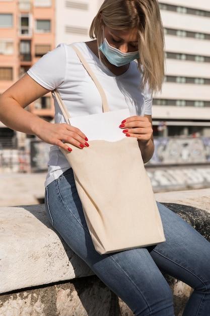 Vrouw die een boodschappentas draagt en een medisch masker draagt Gratis Foto