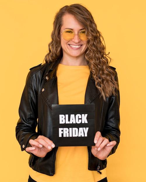 Vrouw die een bril draagt en zwarte vrijdagetiket houdt Gratis Foto