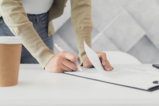 Vrouw die een document close-up ondertekent Gratis Foto