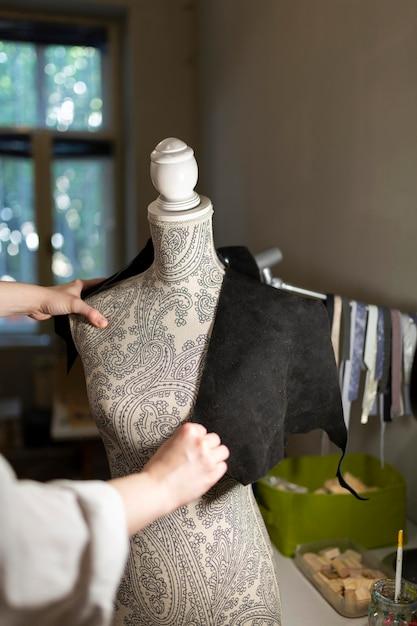 Vrouw die een etalagepop gebruikt om kleding te maken Gratis Foto