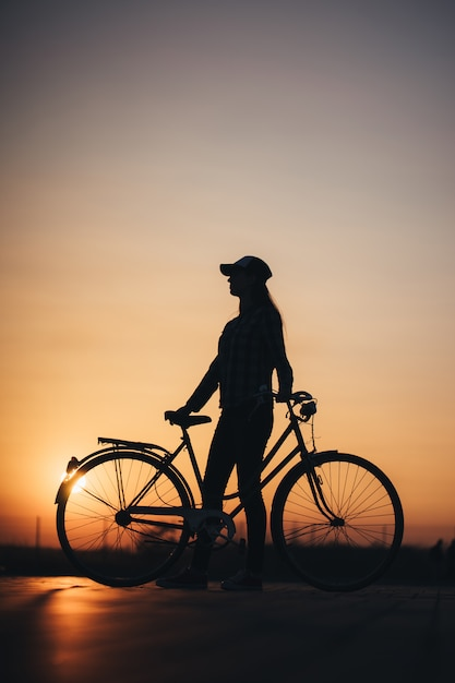Vrouw die een fiets in de stad berijden tijdens zonsondergang Premium Foto