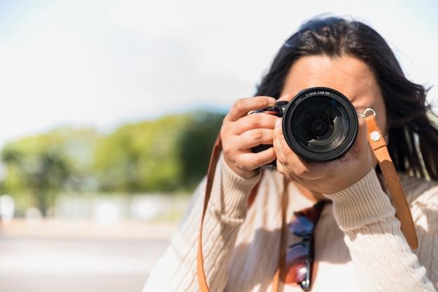 Vrouw die een foto in de loop van de dag met onduidelijk beeldachtergrond nemen Gratis Foto