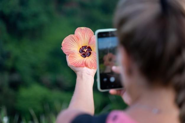 Vrouw die een foto met haar mobiele telefoon neemt van een bloem die ze in haar hand houdt Gratis Foto