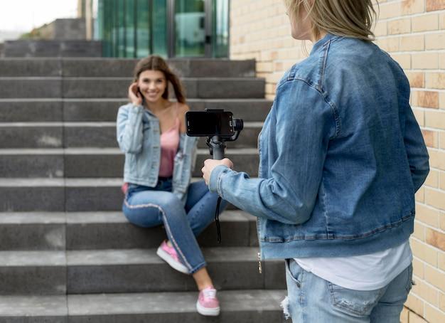 Vrouw die een foto van haar vriend met een smartphone neemt Gratis Foto