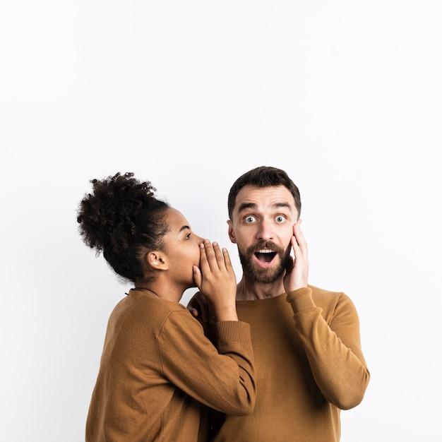 Vrouw die een geheim vertelt aan de verraste man Gratis Foto