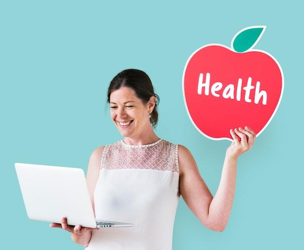 Vrouw die een gezondheidspictogram houdt en laptop met behulp van Gratis Foto