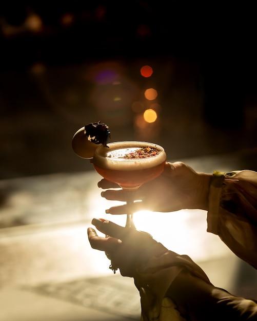 Vrouw die een glas cocktail in zonsondergang houdt Gratis Foto