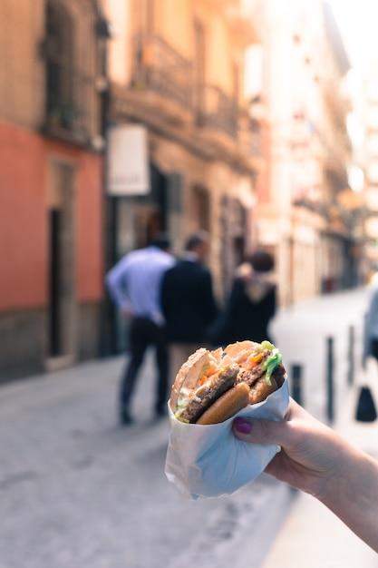Vrouw die een hamburger in handen houdt Premium Foto