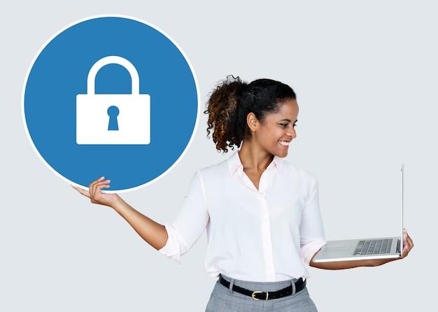 Vrouw die een hangslot en laptop houdt Gratis Foto
