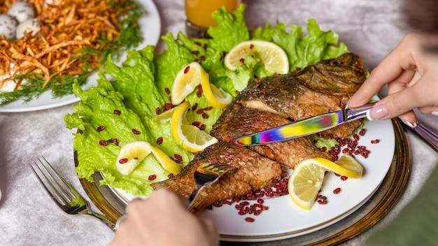 Vrouw die een hele gegrilde vis met een citroen eet Premium Foto