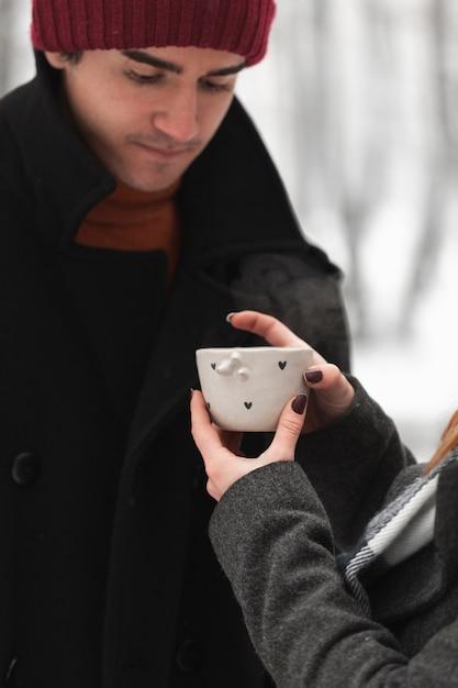 Vrouw die een hete kop thee geeft aan haar vriendje Gratis Foto