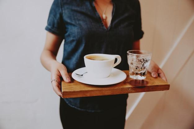 Vrouw die een houten dienblad met koffie en sodawater op het houdt Gratis Foto