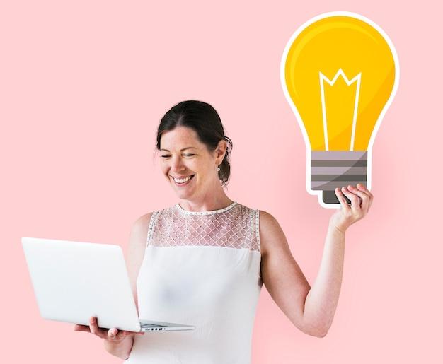 Vrouw die een ideepictogram houdt en laptop met behulp van Gratis Foto