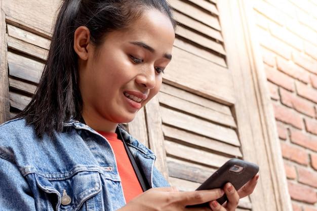 Vrouw die een jasje draagt en met mobiele telefoon speelt Premium Foto