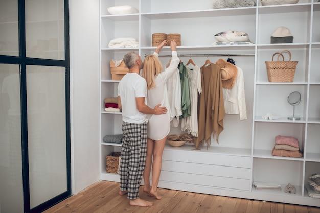 Vrouw die een jurk in een kledingkast kiest en aan haar echtgenoot toont Premium Foto