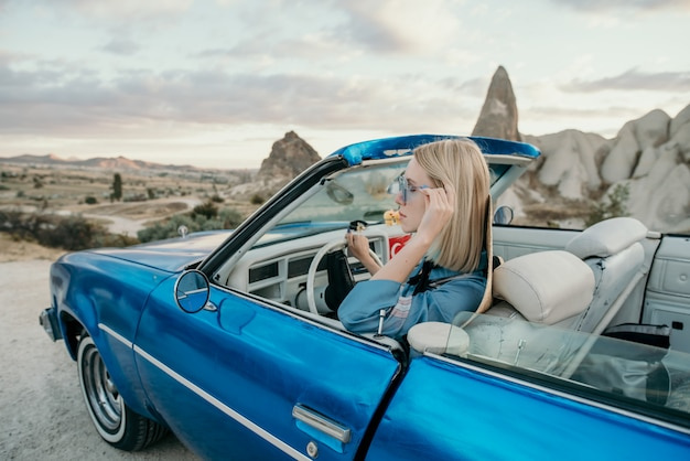 Vrouw die een klassieke blauwe convertibele auto in turkije drijven Premium Foto