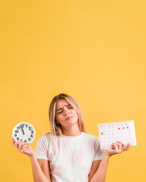 Vrouw die een klok en een menstruele ruimte van het kalenderexemplaar houdt Gratis Foto