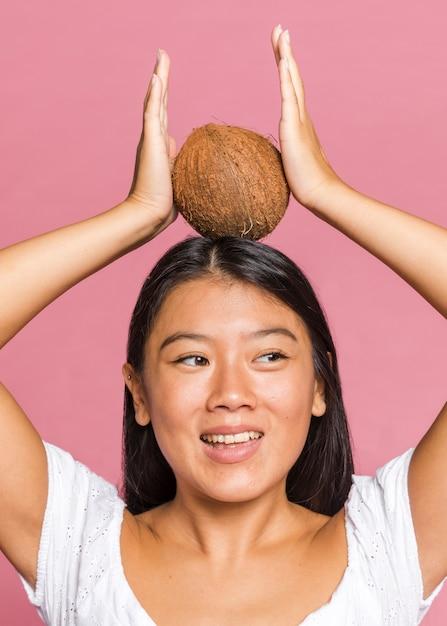 Vrouw die een kokosnoot op haar hoofd houdt Gratis Foto