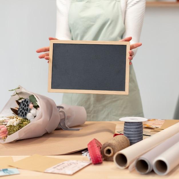 Vrouw die een leeg exemplaar ruimtebord houdt Gratis Foto